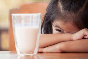 Menina debruçada na mesa com um cara sofrida olhando para um copo de leite por ter alergia à proteína do leite de vaca