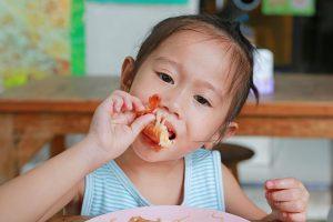 Criança japonesa comendo um camarão, um alimento que causa alergia alimentar, com as mãos