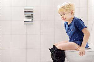 Criança com constipação intestinal sentado no vaso tentando evacuar