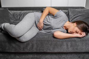Adolescente deitada de olhos fechados em um sofá com um das mãos na barriga e outra no rosto indicando que está sofrendo de alguma dor proveniente de doença inflamatória intestinal