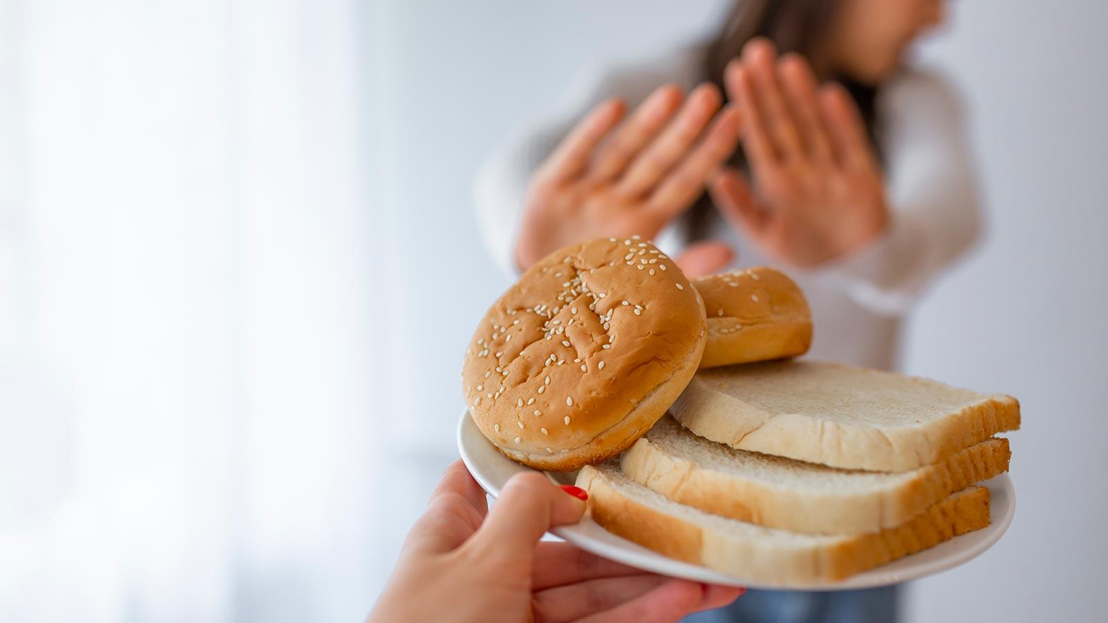 Mão segurando um prato com pães no primeiro plano e, no segundo plano, uma mulher desfocada recusa a comida por ter doença celíaca
